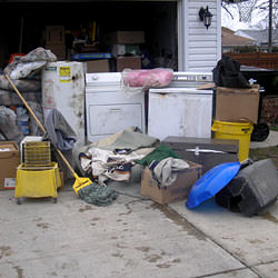 Soaked, wet personal items sitting in a driveway, including a washer and dryer in Sunburst.