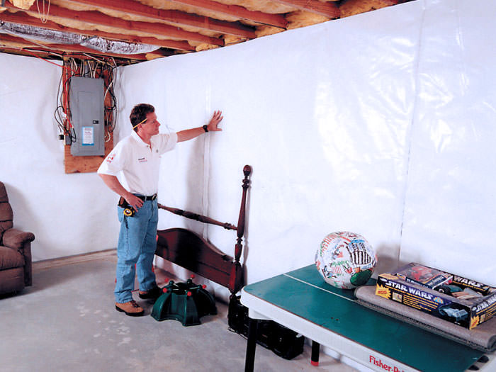 Installation of a vapor barrier on a basement wall in Whitlash